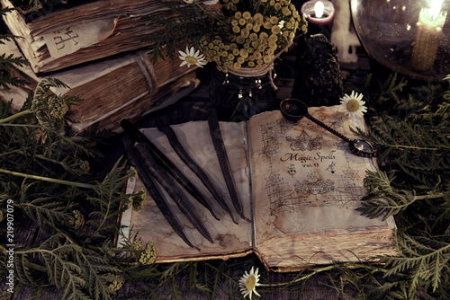 Antique magic book with grunge shabby pages, herbs and black candles. Mystic background with ritual esoteric objects, occult, fortune telling and halloween concept