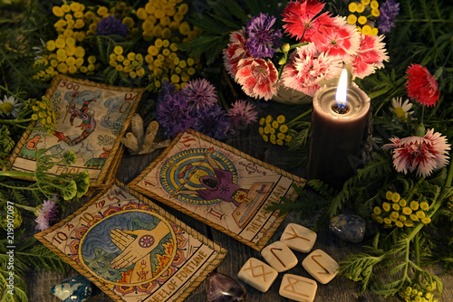 Still life with old tarot cards, black candle, runes, healing herbs and flowers. Mystic background with ritual esoteric objects, occult, fortune telling and halloween concept