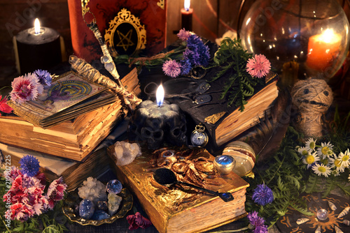 Still life with old witch books, antique lamp, black candles, voodoo doll and ritual objects. Mystic background with ritual esoteric objects, occult, fortune telling and halloween concept
