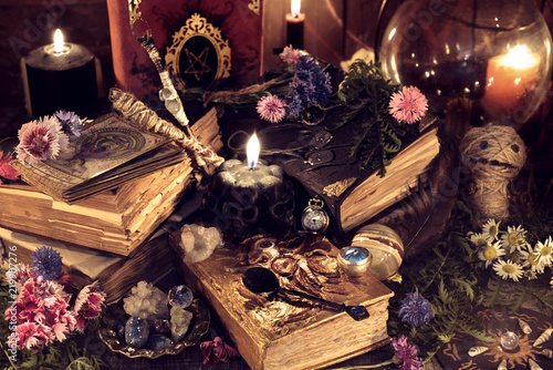 Still life with old magic books and ritual objects in mystic candlelight. Mystic background with ritual esoteric objects, occult, fortune telling and halloween concept