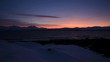 red orange sunset behind snowy mountain range and cold fjord water