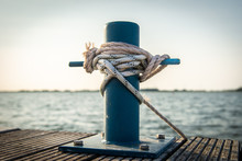 Mooring Bollard With A Rope And A Knot In Front Of Water