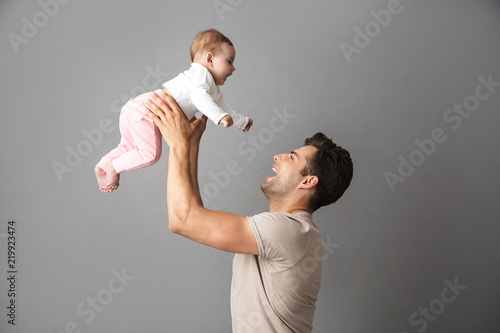 Fotografering Image of happy father man holding his little child in hands, isolated over gray