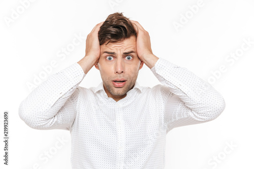 Fotomural Portrait of irritated disappointed man 20s grabbing his head and expressing problem, isolated over white background