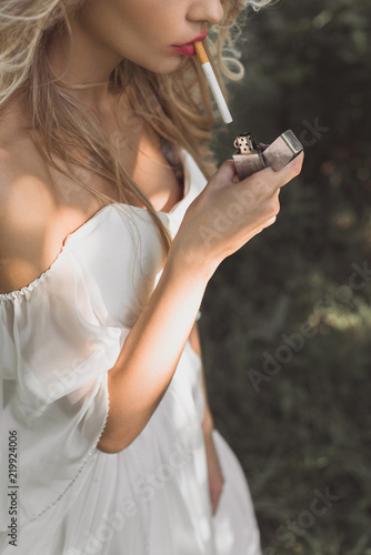 Fotografiet cropped shot of young woman in white dress holding lighter and smoking cigarette