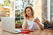 Woman with smart phone. Stunning fashionable girl talking by smartphone, while drinking a coffee at the cafe, woman using a laptop. Workspace for business woman freelancer. Business concept.