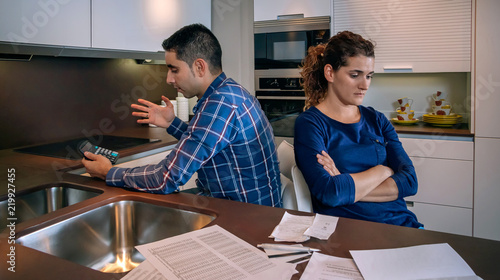 Photo Angry young couple sitting back to back after a hard quarrel by their many debts at home