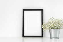 Black A4 Frame Mockup In Interior. Frame Mock-Up Poster Or Photo Frame And Supplies And Vase With Flowers On Table Near White Wall. Desk Space, Copy Space. Background