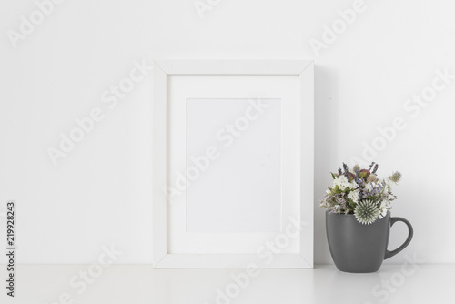 33e49e316a44 White A5 portrait frame mockup with small bouquet of dried flowers ...