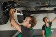 Two young mechanics diagnose the condition of the car's suspension