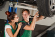 A beautiful and young girl locksmith conducts diagnostics of the suspension of the car with her colleague from the car-care center, they are dressed in green overalls