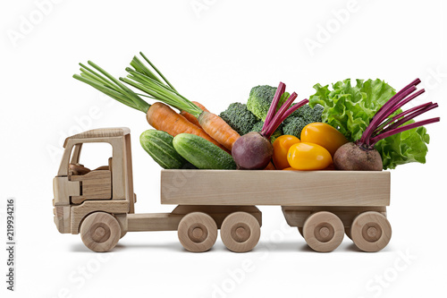 Variety of fresh vegetables in  toy wooden truck.