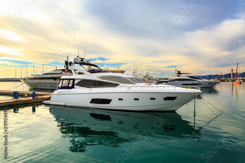 Luxury yachts docked in sea port at sunset. Motor boats  moored at pier in blue water. Relaxation and fashionable vacation.