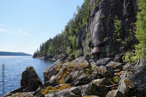 Valokuva  Rocky shore of lake Ladoga, rock, overgrown with forest, in the Bay of Ladoga, rocks covered with mosses