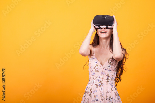 b3e35b9f00e3 Smile happy woman getting experience using VR-headset glasses of virtual  reality in studio over