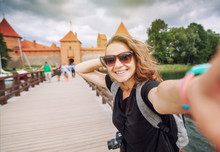 Beautiful Young Woman Tourist Traveler Doing Selfie On A Mobile Phone On A Background Of Trakai Castle On A Lake, Lithuania, Traveling To The Baltic Countries