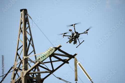 Stampa su Tela Quadcopter flying in a sky, electric pylon, cables and insulators on a background