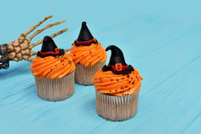Halloween Cupcakes. Witch Hat Cupcake. Halloween Treats On Wooden Blue Background With Palm Of The Skeleton.