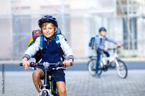Fotografía  Two school kid boys in safety helmet riding with bike in the city with backpacks