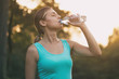 Beautiful woman enjoys drinking water during exercise.