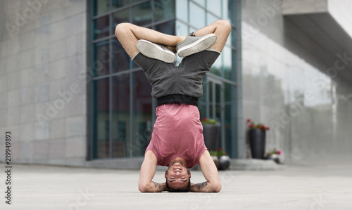 Professional yoga man doing headstand exercise outdoors