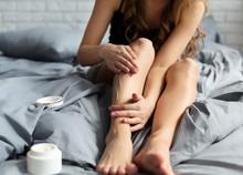 Woman Applying Body Cream On Her Leg