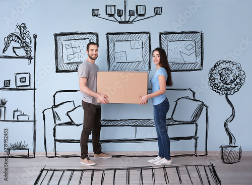 Young couple holding box indoors and imagining interior of new house Canvas-taulu