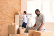 Interracial couple with carton boxes in room. Moving into new house