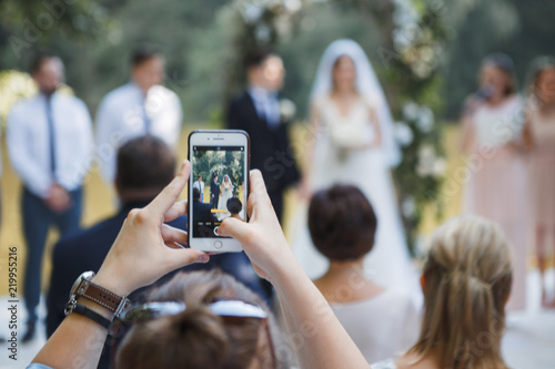 Fotografía  guest at the wedding ceremony takes pictures on the phone of the newlyweds