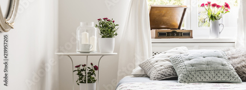 Fotografie, Obraz  Panorama of grey pillows on bed and plant in bright bedroom interior with candles on table