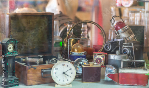 Fotografía  Assorted vintage items, clocks, cameras, flasks, sextant, lamps behind shop window
