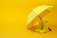 A Pair Of Yellow Rain Boots And A Umbrella On A Yellow