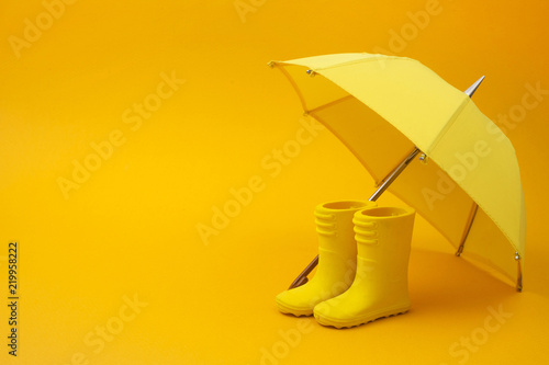 Fotografia, Obraz  A pair of yellow rain boots and a umbrella on a yellow