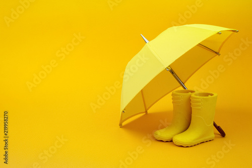 Papiers peints Nature A pair of yellow rain boots and a umbrella on a yellow