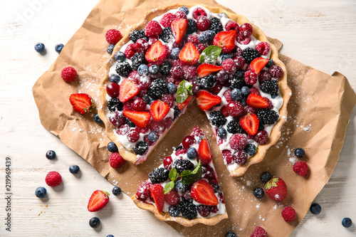 Fotografiet Delicious pie with ripe berries on table, top view