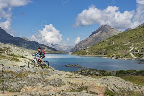 Fototapety, obrazy: senior woman, riding her e-mountainbike on the famous Bernina express trail at Lago Bianco, Bernina Pass near Pontresina an St.Moritz, Engadin, Switzerland