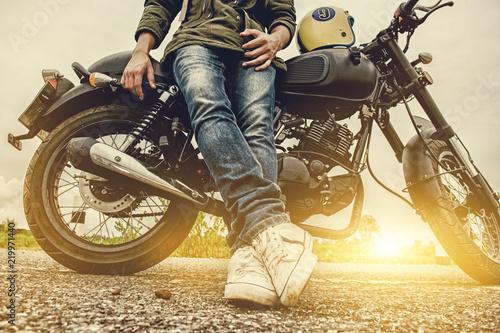 Платно Biker man with his motorbike(motorcycle) on street and beautiful, enjoying freedom and active lifestyle, having fun on a bikers tour