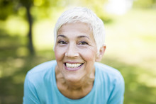 Portrait Of A Smiling Sporty Senior Woman In A Park