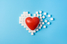 Big Red Heart On Broken Heart Made Of Sugar Cubes On A Blue Background