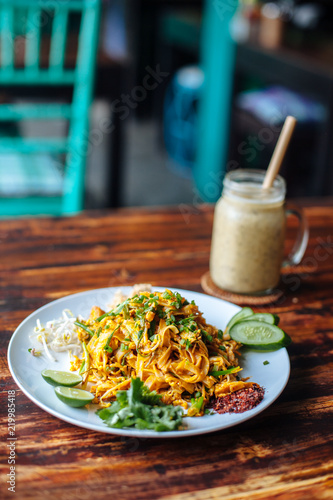 Healthy Vegetarian vegan menu Pad Thai, stir-fried rice noodles, is one of Thailand's national main dish and banana smoothies on wooden table
