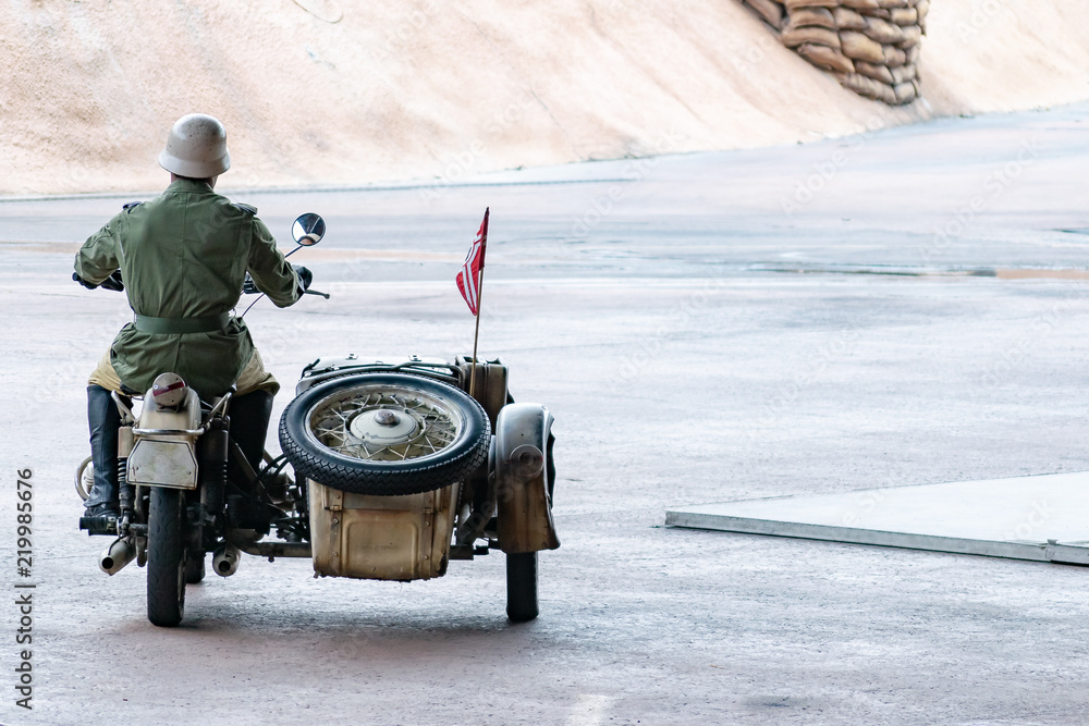 Fototapeta Man wearing green and khaki clothing with helmet and boots, riding motorbike with sidecar