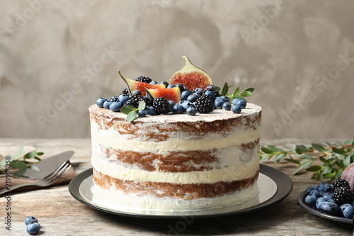 Delicious homemade cake with fresh berries served on wooden table