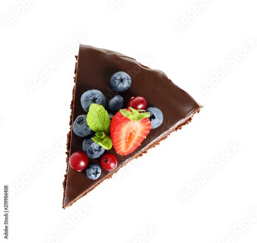 Foto Slice of chocolate sponge cake with berries on white background, top view
