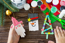 A Child Is Holding Christmas Decoration Or Christmas Gift Wooden Sticks. Handmade. Project Of Children's Creativity, Handicrafts, Crafts For Kids.