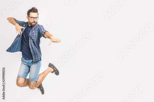 Happy excited cheerful young man jumping and celebrating success isolated on a w Fototapeta