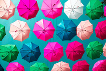 Multicolored Floating Umbrellas Against The Blue Sky.