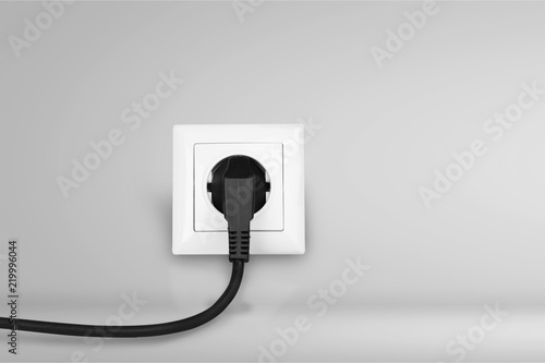 White electrical plug in the electric socket on a wall