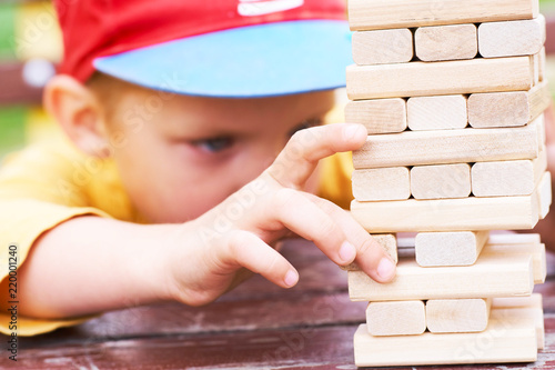 Fotografía  Caucasian kid is playing wood blocks tower game for practicing physical and mental skill