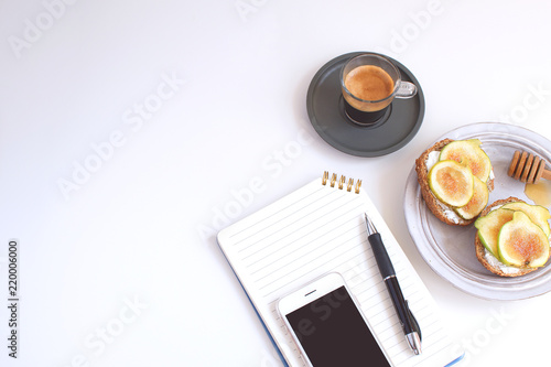 Obraz na plátne Worktable Business concept Table Back to school Notepad Cellphone Pen Black coff