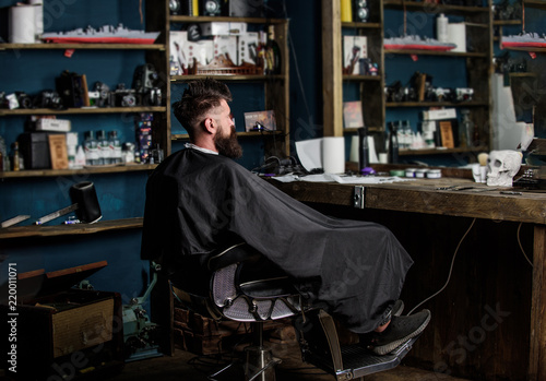 Fényképezés Man with beard covered with black cape sits in hairdressers chair in front of mirror